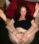 on her back, legs up, and fingering her wet pussy