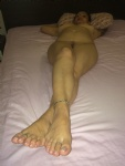 Completely naked on the bed..